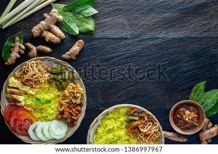 Traditional popular Indonesian breakfast nasi kuning/yellow rice served with shredded chicken, chili, sweet crispy tempe, fried noodle, sliced tomato & cucumber, stir fry bean, omelette eggs