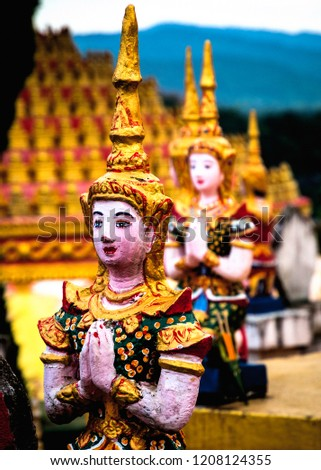 Traditional Praying Buddhist Figurines at Outdoor Shrine on Religious Hill Top. Portrait Orientation. (Huay Xai, Bokeo, Laos). #1208124355