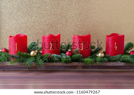 traditional red advent candles with numbers and branch of fir with christmas baubles on gold background #1160479267
