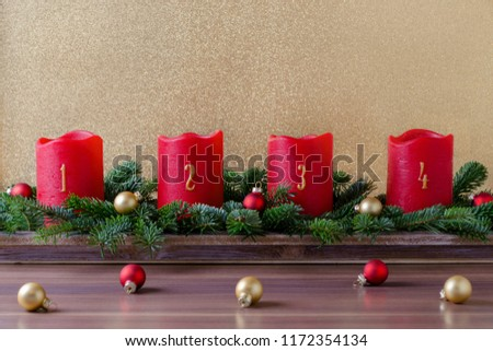 traditional red advent candles with numbers and christmas decoration, branch of fir with baubles on gold background #1172354134