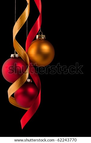 Traditional red and gold Christmas ball ornaments with ribbons on black