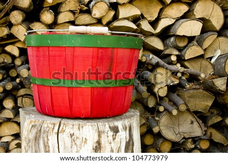 traditional red and green bushel basket with a rustic log pile background