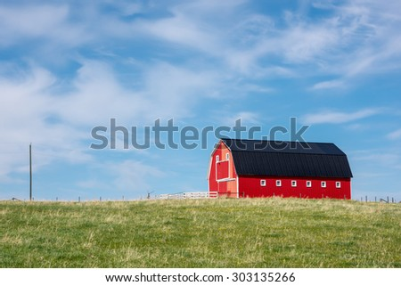 Traditional red barn with white trim in open pasture with blue sky & a few clouds