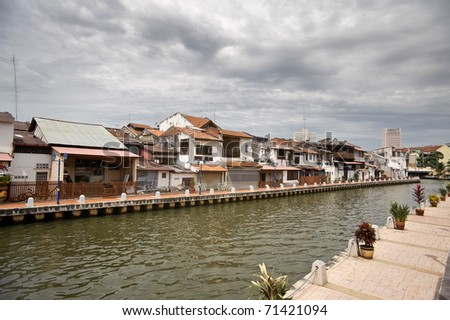 Traditional red brick and white walls of the house and sidewalk of river bank in Malacca, Malaysia, asia