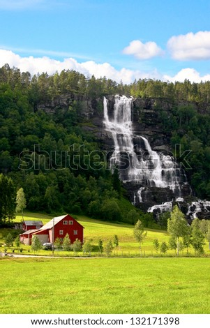 Traditional red farm next to a waterfall and green field in Norway.