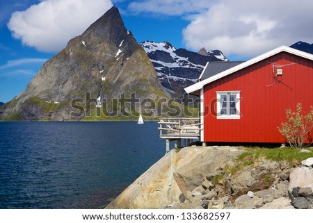 Traditional red fishing hut by fjord on Lofoten islands in Norway