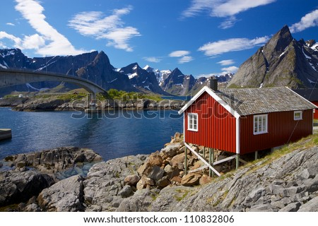 Traditional red fishing rorbu hut on Lofoten islands in Norway near bridge connecting islands