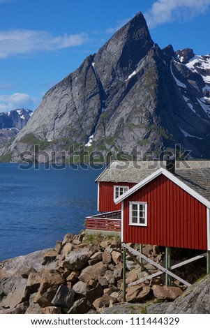 Traditional red fishing rorbu hut on the coast of fjord on lofoten islands in Norway