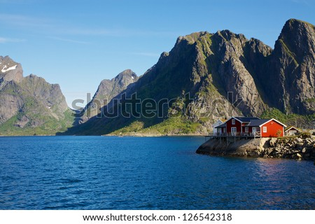 Traditional red house by scenic fjord on Lofoten islands in Norway