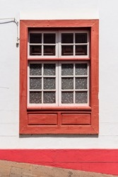 Traditional red painted window in canarian colonial style house in the old town of Santa Cruz de La Palma, in the quarter of San Sebastian, also known as La Canela