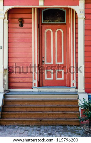 Traditional red painted wooden door and porch