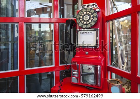 Traditional red telephone booth in London with a desaturated background