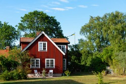 Traditional red wooden house in Sweden on the island Oland, in the summer. The house is surrounded by a beautiful, summery garden