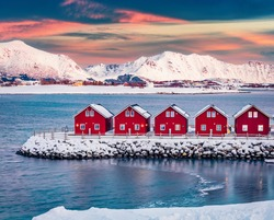 Traditional red wooden houses on the shore of Offersoystraumen fjord. Fantastic winter sunset on Vestvagoy island. Picturesque evening view of Lofoten Islands, Norway, Europe.  Life over polar circle.