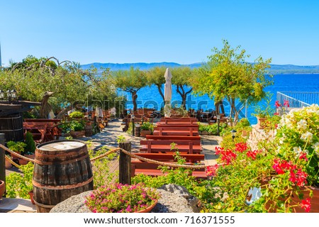 Traditional restaurant decorated with flowers and wine casks with sea view in Bol town, Brac island, Croatia #716371555