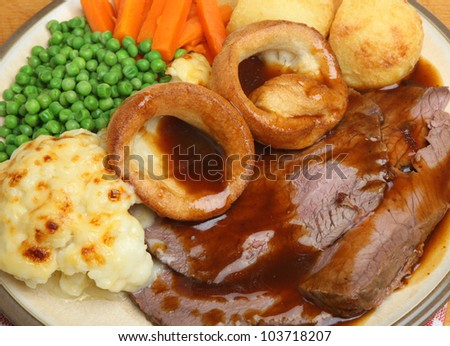 Traditional roast beef dinner with Yorkshire pudding, vegetables and gravy.
