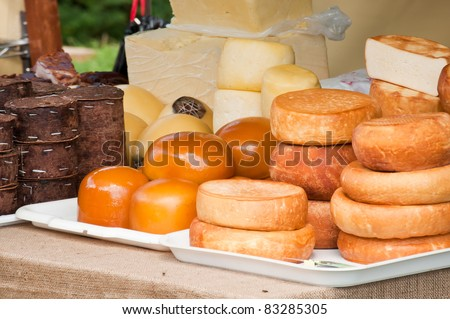 Traditional Romanian cheese varieties displayed by a farmer at a medieval fair