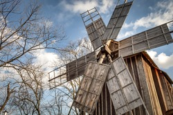 Traditional romanian windmill used by the romanians to grind grains for centuries, against a blue cloudy sky and surrounded by trees