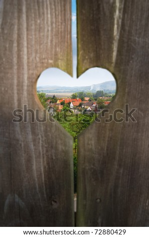 Traditional rural hospitality, looking through a heart shaped window on a wooden door to a landscape with a village.