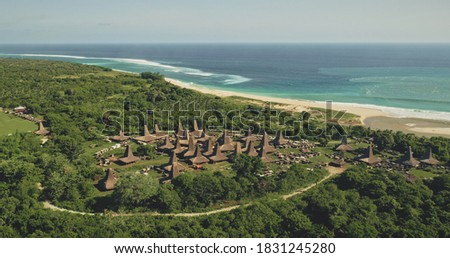 Traditional rural houses at Kodi village, Sumba Island, Indonesia. Aerial view of tropic countryside with buildings landmark at sea bay coast. Cinematic drone shot of summer vacation Zdjęcia stock ©