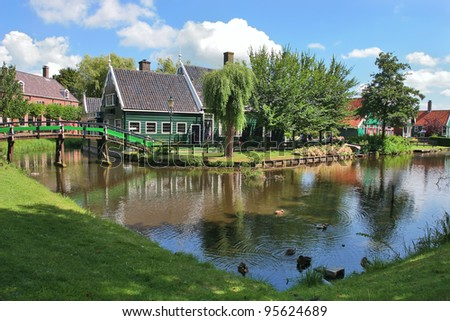 Traditional rural houses on green lawns along creek in Zaanse Schans - small village and popular touristic site in Holland (Netherlands). - stock photo