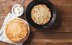 Traditional Russian Crepes Blini stacked in a plate and pancake in a cast-iron frying pan on dark wooden table. Maslenitsa traditional Russian festival meal. Russian food, russian kitchen. Top view.