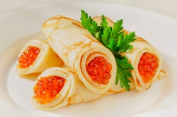 Traditional Russian Crepes Blini stacked in a plate with red caviar and parsley on light background. Maslenitsa traditional Russian festival meal. Russian food, russian kitchen. Space for text