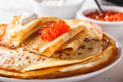 Traditional Russian Crepes Blini stacked in a plate with red caviar, fresh sour cream on light background. Maslenitsa traditional Russian festival meal. Russian food, russian kitchen. Close up.