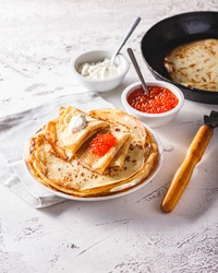 Traditional Russian Crepes Blini stacked in a plate with red caviar, fresh sour cream on light background. Maslenitsa traditional Russian festival meal. Russian food, russian kitchen