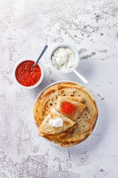 Traditional Russian Crepes Blini stacked in a plate with red caviar, fresh sour cream on light background. Maslenitsa traditional Russian festival meal. Russian food, russian kitchen. Top view.