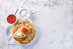 Traditional Russian Crepes Blini stacked in a plate with red caviar, fresh sour cream on light background. Maslenitsa traditional Russian festival meal. Russian kitchen. Top view. Space for text