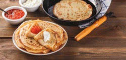 Traditional Russian Crepes Blini stacked in a plate with red caviar, fresh sour creamon dark wooden table. Maslenitsa traditional Russian festival meal. Russian food, russian kitchen. Long wide banner
