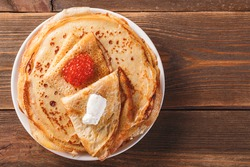 Traditional Russian Crepes Blini stacked in a plate with red caviar, fresh sour creamon dark wooden table. Maslenitsa Russian festival meal. Russian food, russian kitchen. Top view. Space for text
