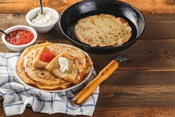 Traditional Russian Crepes Blini stacked in a plate with red caviar, fresh sour creamon dark wooden table. Maslenitsa traditional Russian festival meal. Russian food, russian kitchen