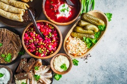Traditional Russian cuisine concept. Borsch, jellied meat, bacon, pancakes, salad vinaigrette and sauerkraut, copy space, gray background.