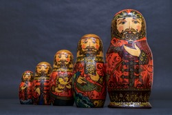 Traditional Russian matryoshka dolls lined up against gray background, doll within a doll, object within an object, metaphor for shell companies, Russian nesting doll 4