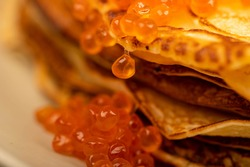 Traditional Russian pancakes with red salmon caviar. Shrovetide week of the meeting of spring. Seeing off winter. Close-up, selective focus.