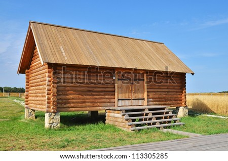 Traditional russian rural wooden house with green grass