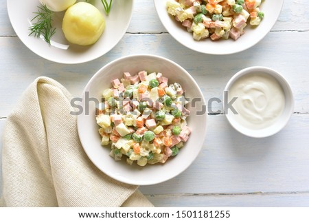 """Traditional russian salad """"Olivier"""" from boiled vegetables and sausage with sauce in bowl. Russian New Year or Christmas salad on light background. Top view, flat lay"""