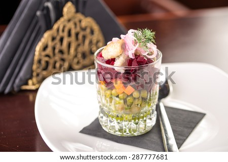 Traditional russian salad with salted herring and beet root on table at restaurant