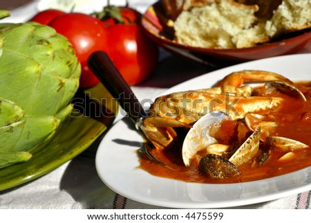 Traditional San Francisco meal of a bowl of cioppino, artichokes and fresh sourdough bread set outdoors on a vintage tablecloth. - stock photo