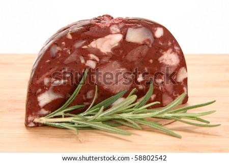Traditional sausage: Headcheese on wooden background decorated with rosemary