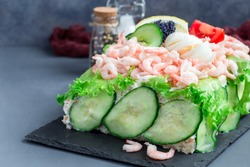 Traditional savory swedish sandwich cake Smorgastorta with a bread, shrimps, eggs, caviar, dill, mayonnaise, cucumber and lettuce, vertical, copy space