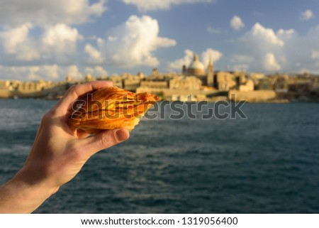 Traditional savoury pastry Pastizzi from Malta with ricotta filling. Valletta on background