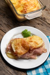 Traditional scalloped potatoes with ham and cheese on wooden background