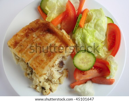 Traditional seafood pie, with fish in bechamel sauce topped with mashed potato and baked, served with a salad, high angle view
