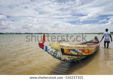 Traditional Senegalese boat on the river with a man and a beautiful sky in the background. Africa, Senegal #526237105