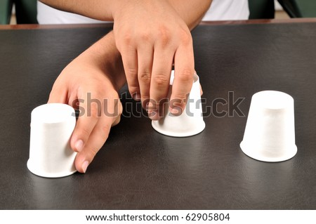 Traditional shell game with three cups - a series of SHELL GAME images.