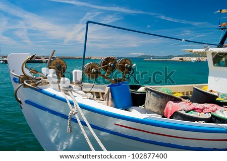 Traditional small Greek fishing boat in a harbor