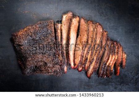 Traditional smoked barbecue wagyu beef brisket offered as top view on an old rustic board with copy space